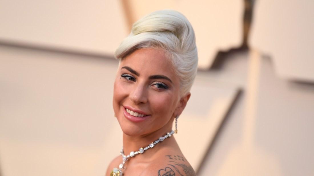 Lady Gaga con un collar y aretes de diamantes blancos con una piedra amarilla la centro