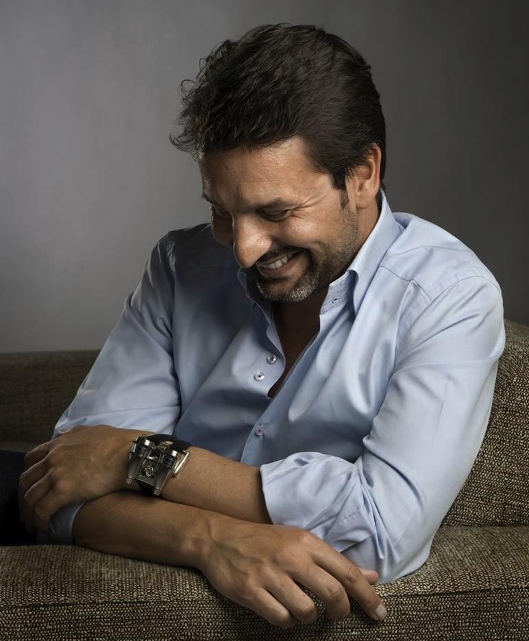 Max Büsser fundador de MB&F sentado en un sillón café con camisa azul y sonriendo