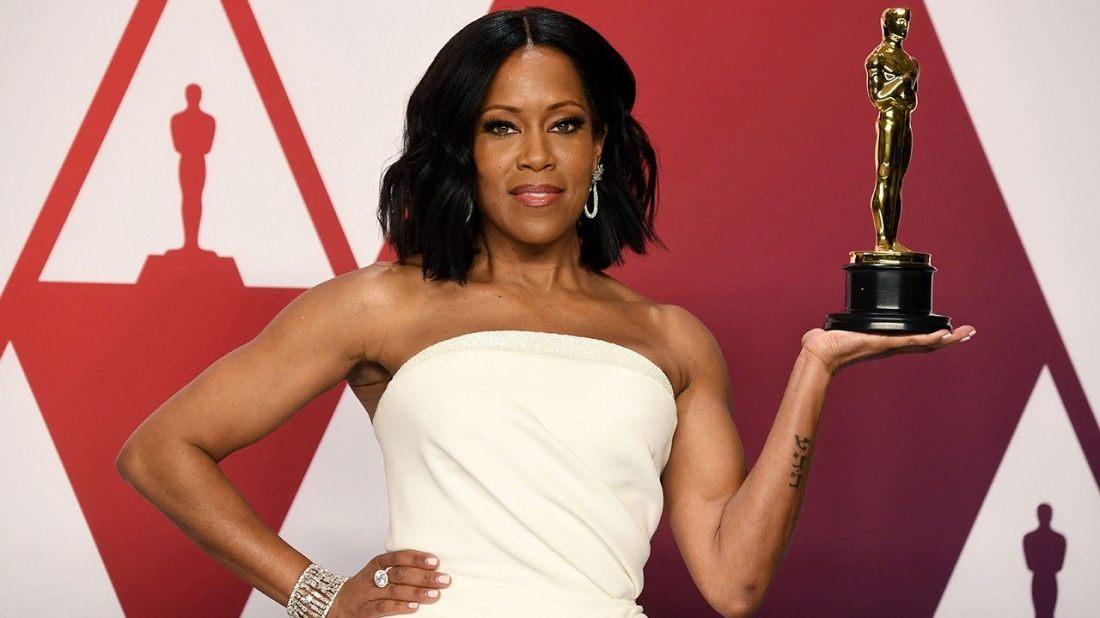 Regina King con vestido blanco y estatuilla del Oscar en la mano