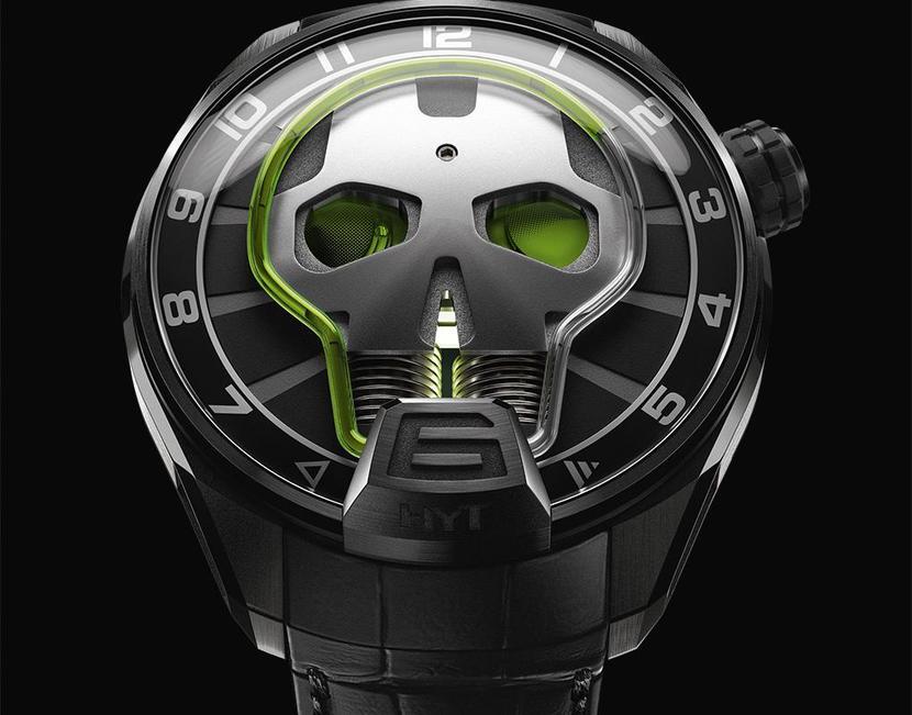 Reloj en color negro con detalles plateados y figura al centro con líquido en color verde