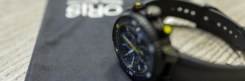 Reloj Oris en color negro con detalles en amarillo y blanco sobre una mesa