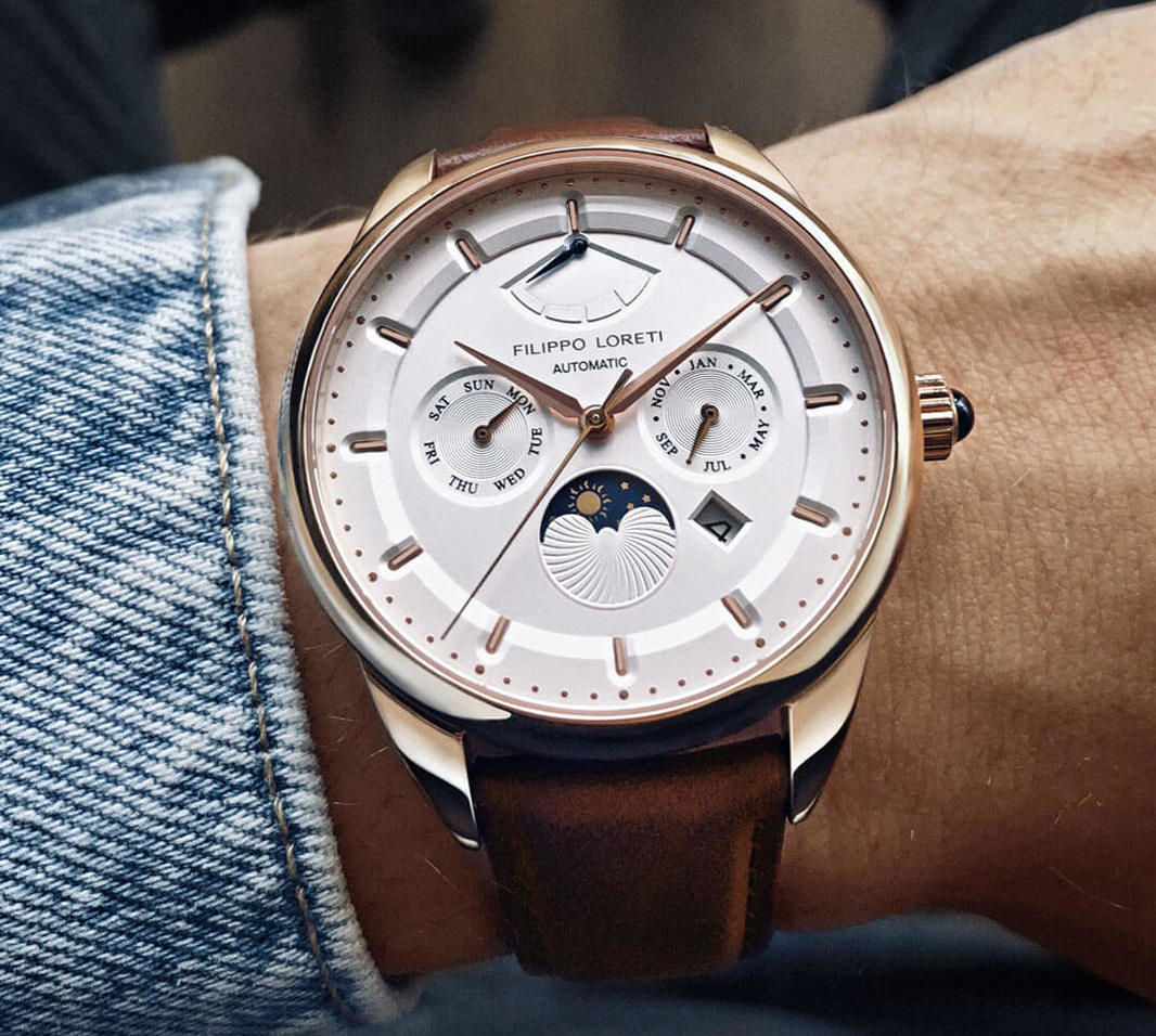 Reloj con correas cafes, caratula en color plateado y dial blanco