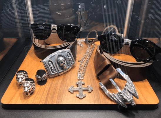 Lentes, cinturones, anillos y collar de plata dentro de una vitrina