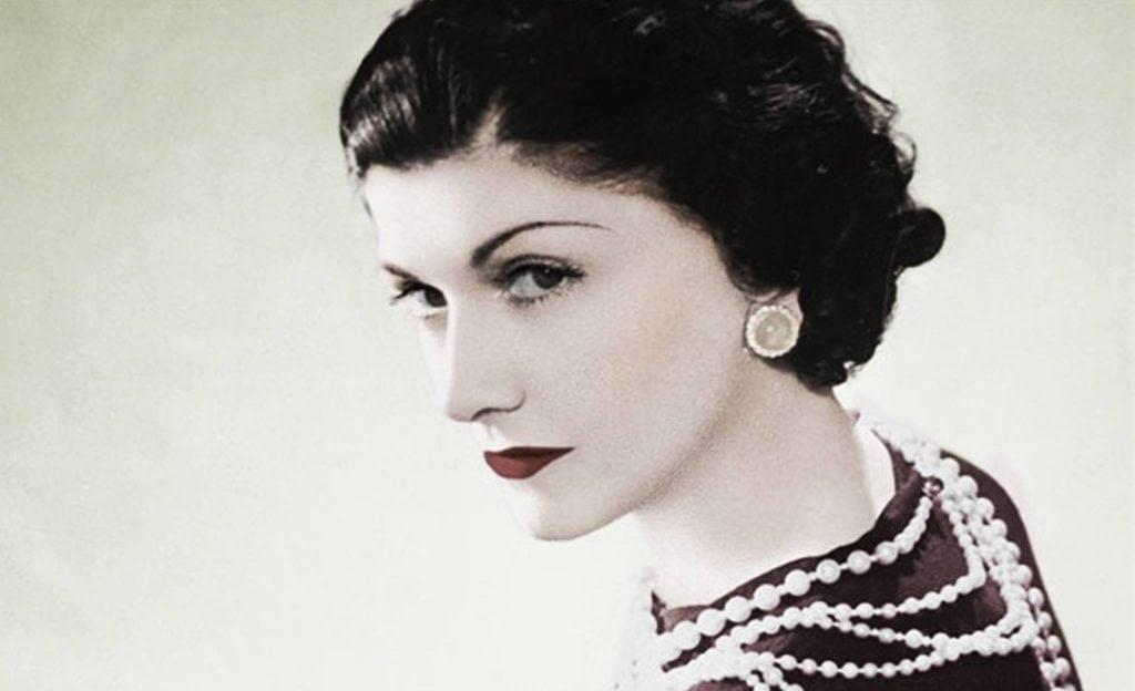 Gabrielle Chanel de perfil usando un collar de perlas y aretes grandes