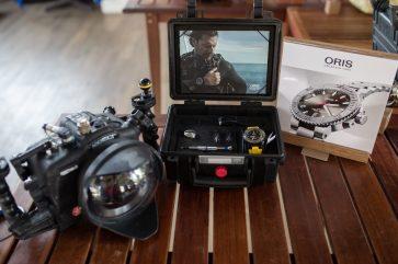 Cámara y estuche con reloj Oris sobre una mesa de madera