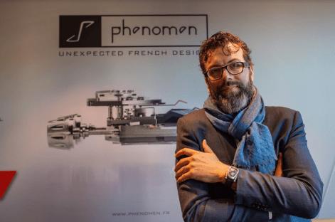 Hombre de traje con lentes usando un reloj en la muñeca frente a la leyenda Phenomen