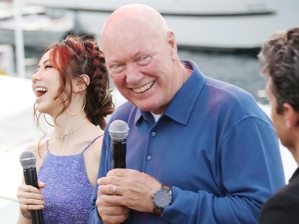 Jean-Claude Biver con playera azul y un micrófono en las manos a lado de una mujer con vestido azul