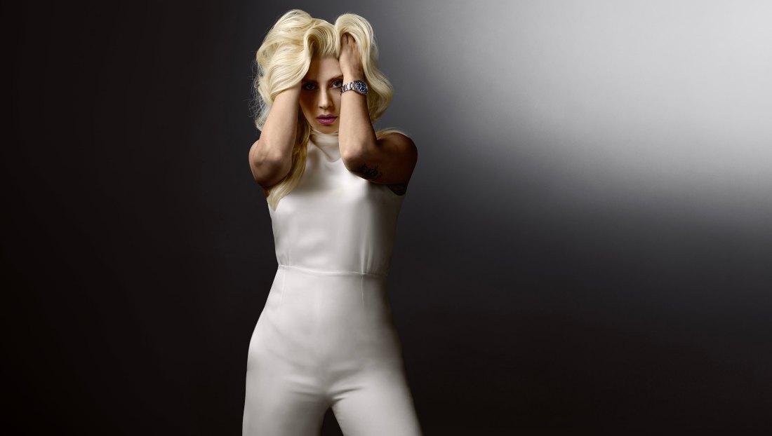 Lady Gaga de frente vestida de blanco agarrandose el cabello