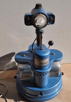 Lavadora suprema en color azul con pequeños recipientes de vidrio a los lados