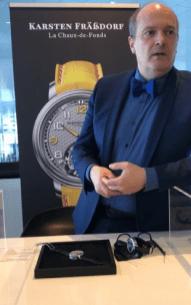 Karsten con saco y camisa azul frente a un estuche con un reloj