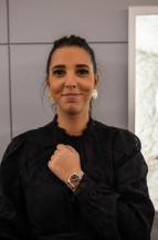Mujer con blusa negra y reloj Tudor en el brazo