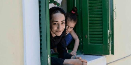 Mujer y niña asomandose por una ventana de color verde