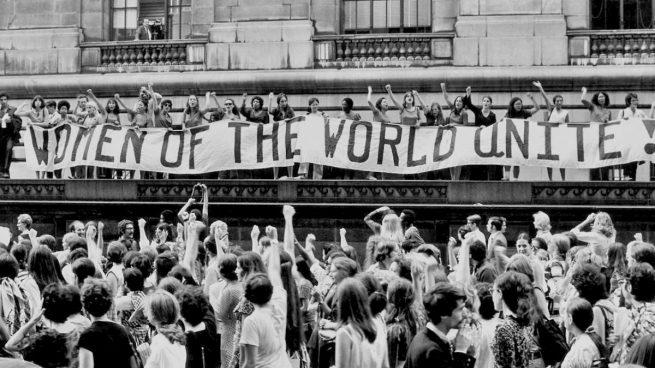 Mujeres con el puño arriba y una pancarta con la leyenda Mujeres de el mundo unidas