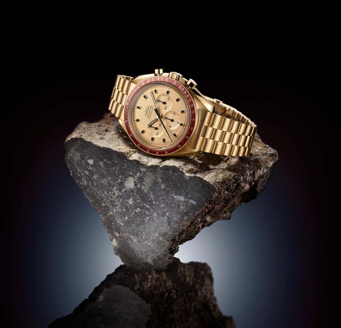 OMEGA Speedmaster Apolo 11 en color oro con detalles en rojo sobre una roca