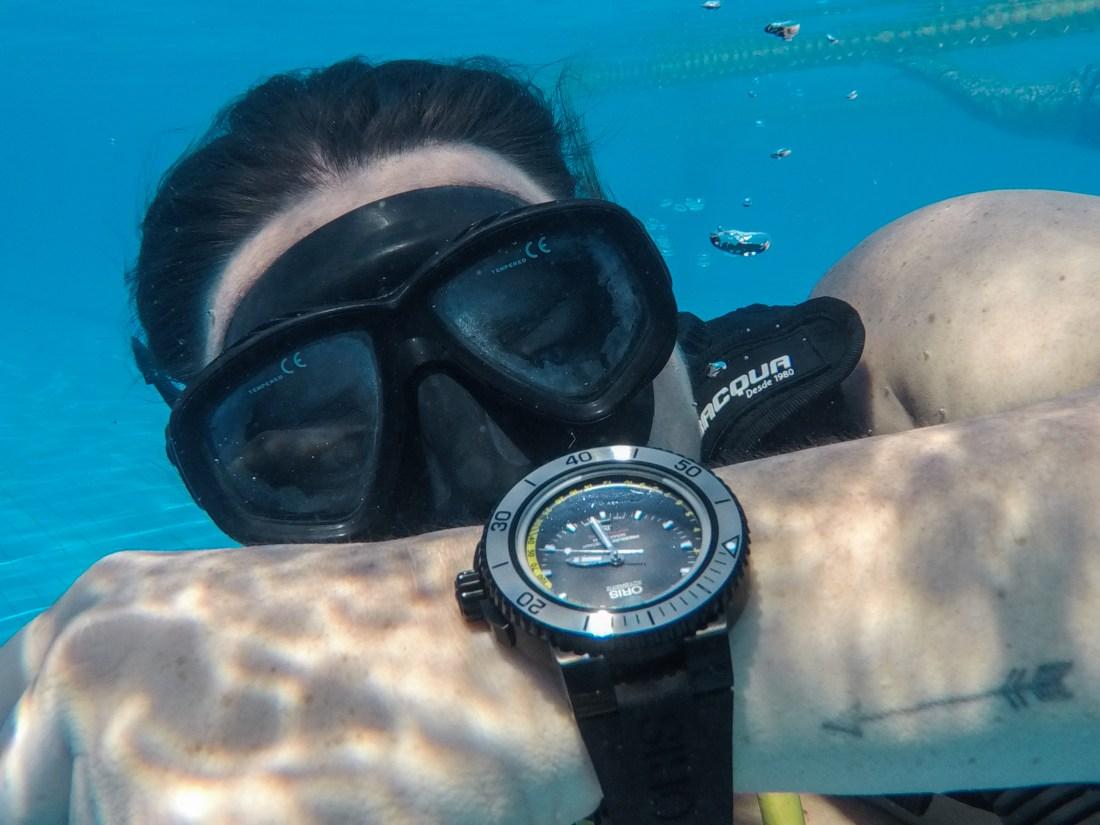 Imagen de buzo bajo el agua con reloj en mano
