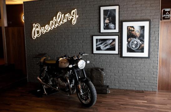 Pared con las letras Breitling, cuadros de relojes y una motocicleta