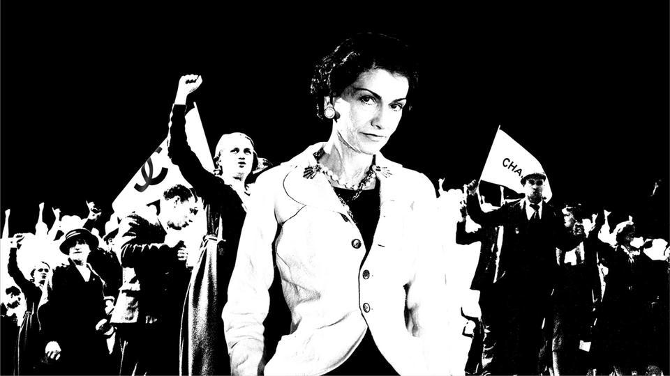 Gabrielle Chanel con protestantes detras de ella fotografia en blanco y negro