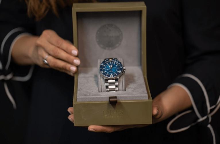Reloj Oris en color plata con el centro azul denro de un estuche