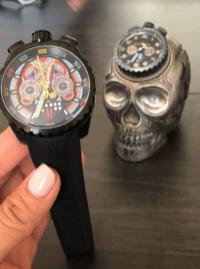Reloj en color negro con una calavera de colores en el centro y al fondo un cráneo en plata
