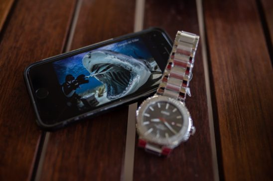 Reloj Oris junto a celular sobre una mesa de madera