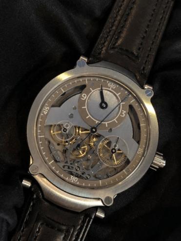 Reloj con correas de cuero en color negro con detalles en plateado y engranajes en el centro