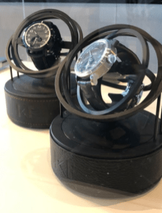 Relojes en color negro con detalles en plata dentro de una vitrina