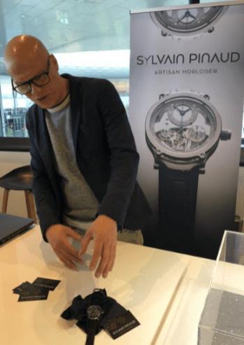 Sylvain Pinaud con sueter gris y saco negro explicando sobre su nuevo reloj