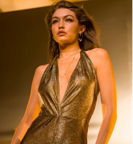 Gigi Hadid de frente con el cabello suelto y blusa en dorado