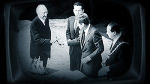 Imagen es escala de grises de cuatro hombres con traje sonriendo