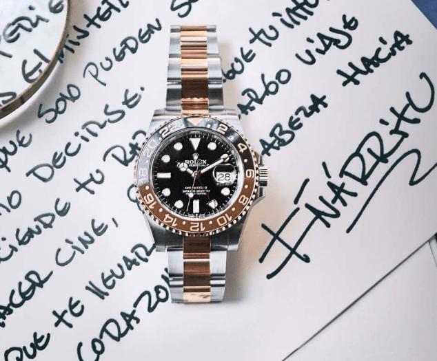 Reloj en color plateado con dorado y caratula negra sobre una hoja con texto