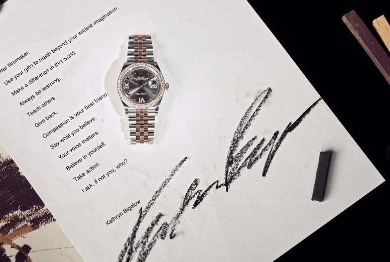 Reloj en color platada con dorado y caratula en plata con diamantes al rededor sobre una hoja con texto