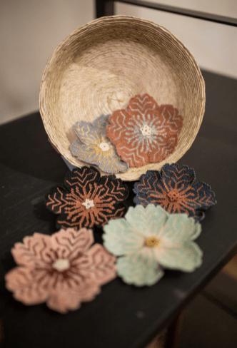 Canasto de lado con flores echas de chaquira de difertentes colores sobre una mesa