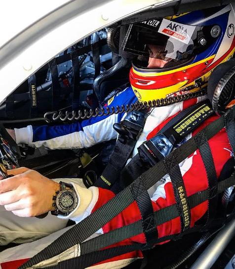 Hombre dentro de un auto de carreras con traje especial y casco