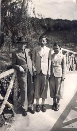 Hombre con sus hijos vestidos con traje sobre un puente