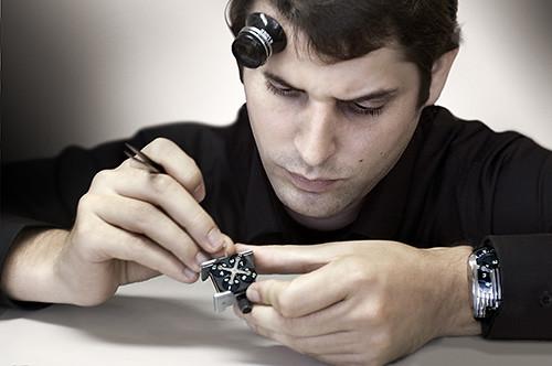 Hombre con una pieza de reloj, unas pinzas en la manos y una lupa de ojo