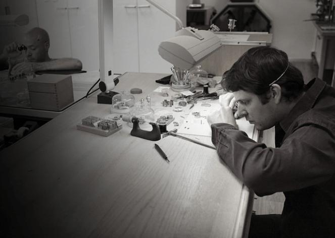 Hombre frente a una mesa con herramientas para elaborar relojes