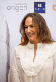 Mujer con vestido blanco y cabello suelto sonriendo