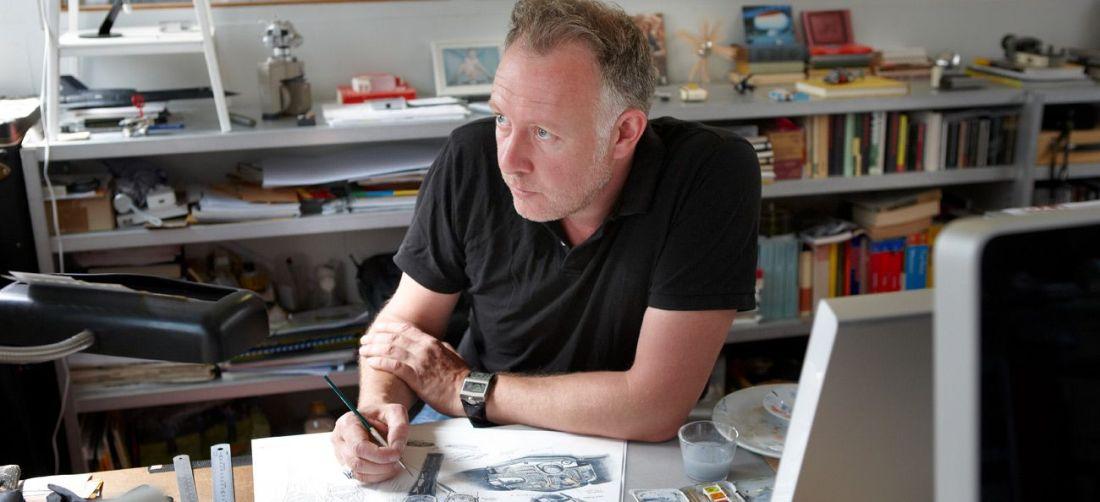 Hombre en una oficina sentado haciendo bocetos de un reloj