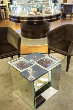 Mesa de vidrio con revistas encima y a los lados sillones aterciopelados