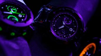 Imagen en tono morado de relojes con detalles en verde y naranja