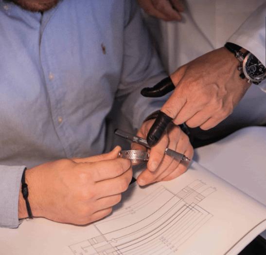 Imagen de unas manos de hombre sosteniendo piezas de reloj sobre hojas blancas