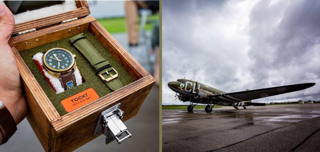 Reloj con correas en verde y café dentro de un estuche de madera y a lado la imagen de un avión