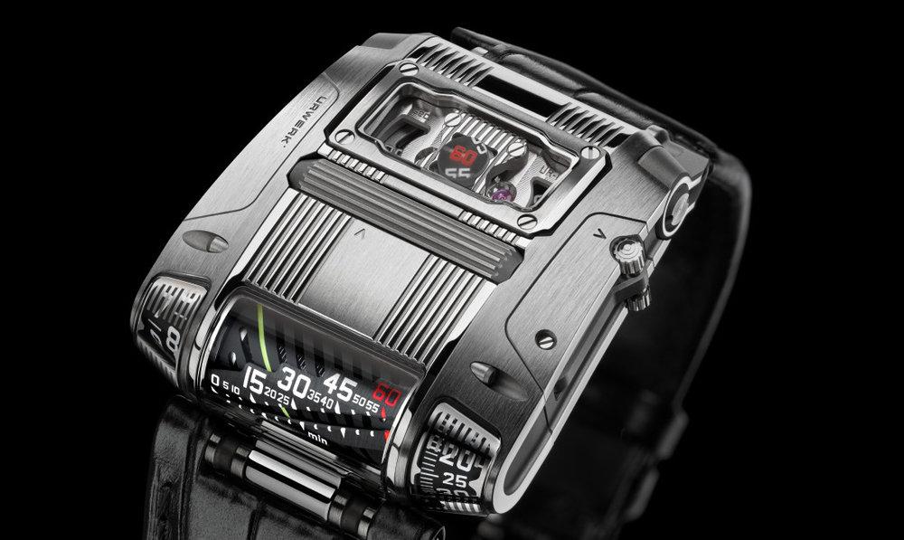 Reloj Urwerk con correas negras y caratula cuadrada color plata con detalles en blanco, negro y rojo