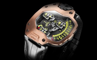 Reloj con correas negras y detalles en color dorado con verde