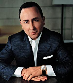 Carlos Dias con saco negro y camisa blanca y un reloj en la mano sentado