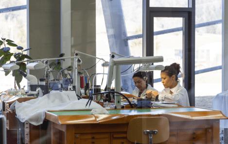 Mujeres con bata blanca sentadas en mesas con herramientas de relojería