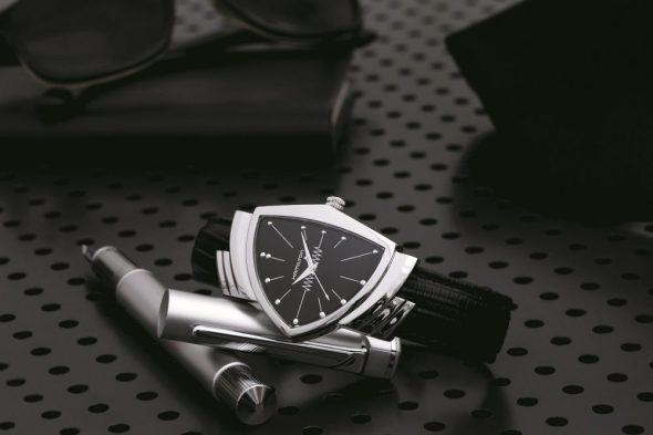 Reloj con correas negras y caratula en color plateado con negro sobre una pluma plateada