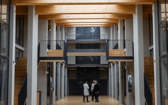 Tres personas dentro del edificio con escaleras y muros blancos