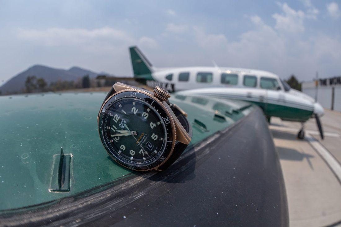Reloj con correas negras y caratula dorada sobre la ala de un avión en color blanco con verde y negro