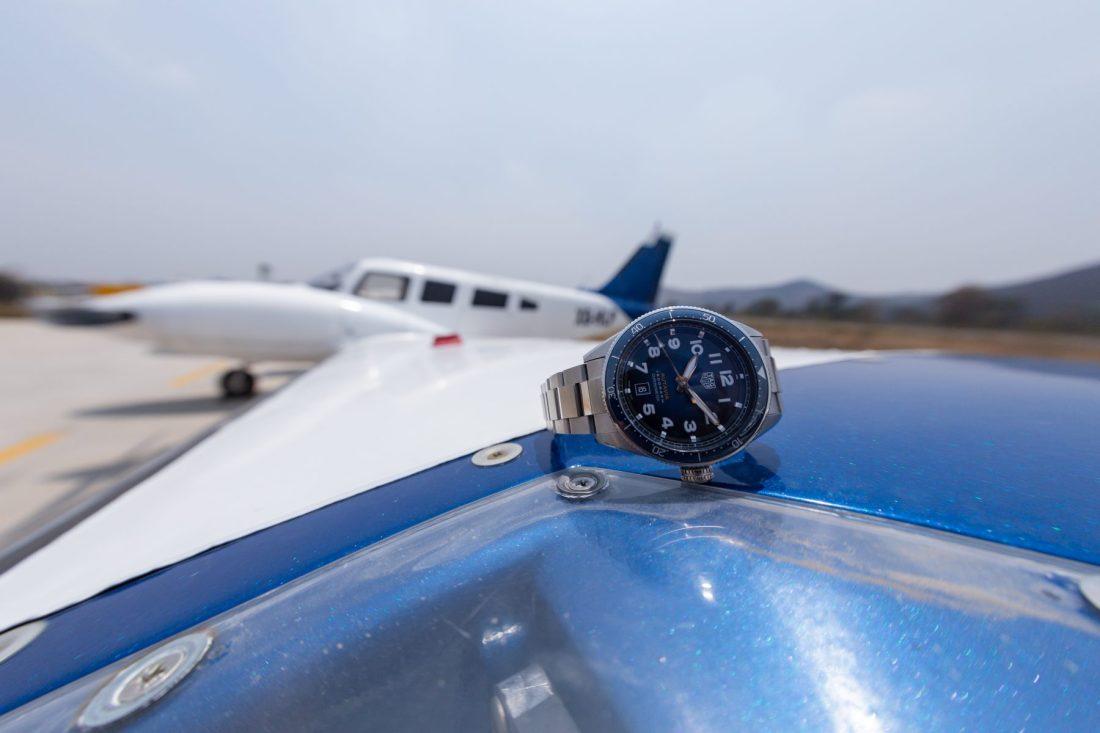 Reloj plateado con caratula azul sobre el ala de un avion de color blanco con azul